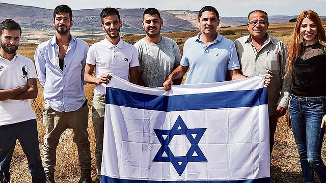 Grupo de jóvenes árabes israelíes sosteniendo una bandera israelí