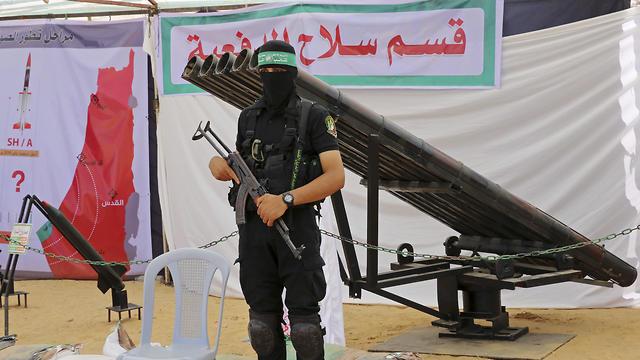 Un militante de Hamas parado junto a un lanzador de misiles