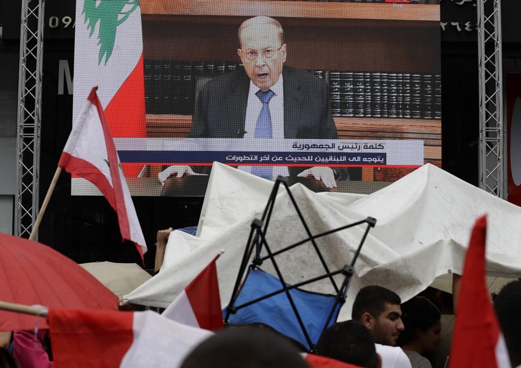Manifestantes libaneses miran el discurso televisado del presidente Aoun