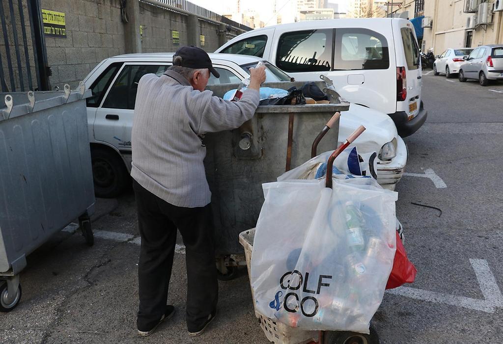 Un anciano busca botellas de plástico en la basura para intercambiarlas por dinero