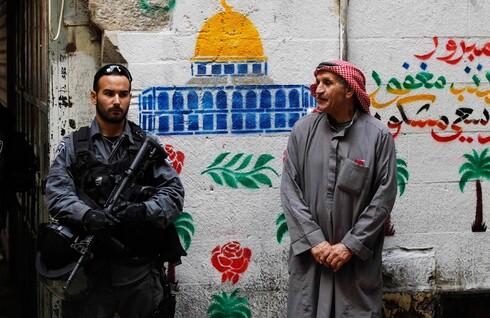 Un oficial de la Policía de Fronteras se encuentra al lado de un residente musulmán local en Jerusalem Este