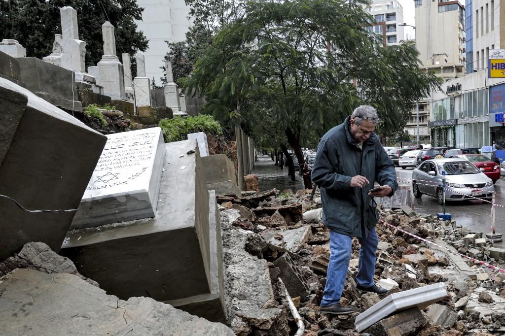 Un hombre inspecciona los daños en las tumbas del cementerio judío