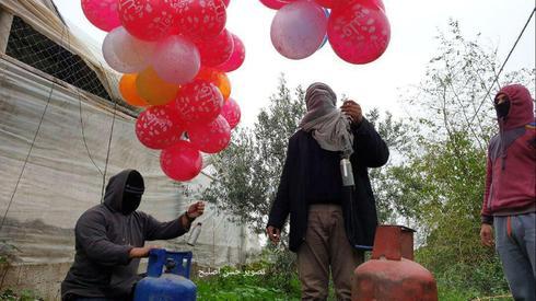 Terroristas palestinos se preparan para lanzar globos incendiarios hacia Israel