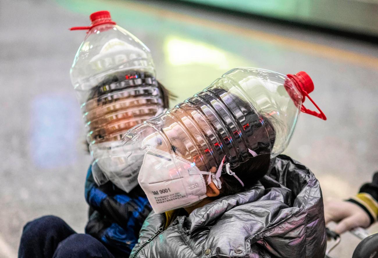 Niños chinos en el aeropuerto de Beijing usan botellas de agua vacías son máscaras improvisadas para no contraer el coronavirus