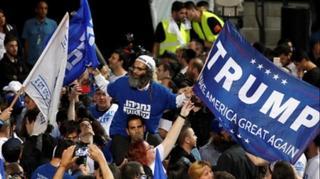 Simpatizantes del Likud portando carteles de apoyo a Trump.