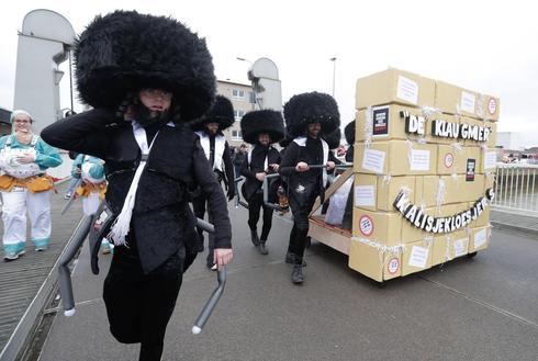 La gente se viste como caricaturas de judíos ortodoxos con una simulación del Muro de los Lamentos