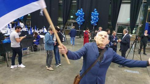 Partidario del Likud con una máscara de Netanyahu puesta