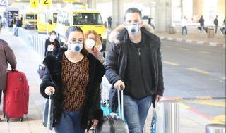 Viajeros llegan al aeropuerto Ben Gurión provistos de máscaras.