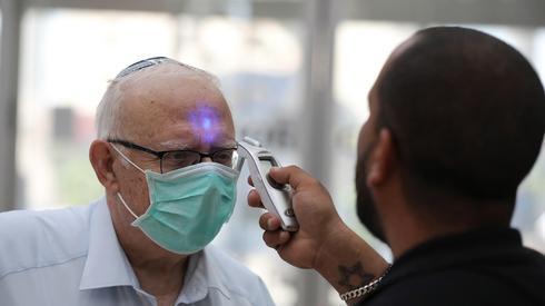 Un hombre mayor procede a tomarse la temperatura en un hospital de Tel Aviv