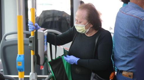 Anciana con máscara quirúrgica en un bus de Tel Aviv