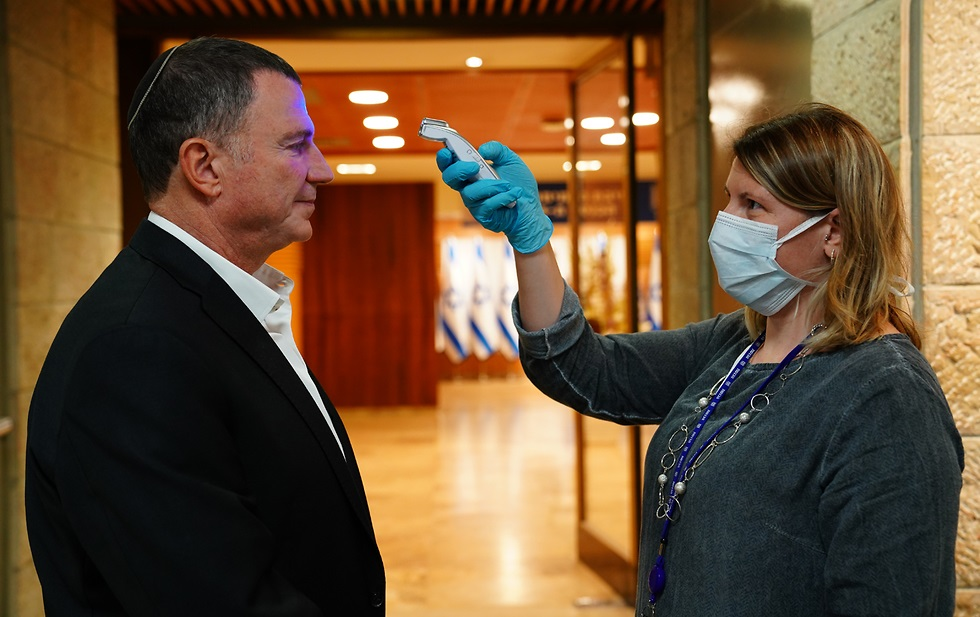 Una jura diferente: Yuli Edelstein, presidente de la Knesset, es revisado por personal de salud antes de ingresar al recinto.