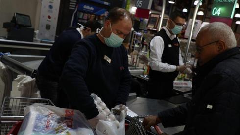 Ciudadanos de Gaza con máscaras protectoras compran en un supermercado.