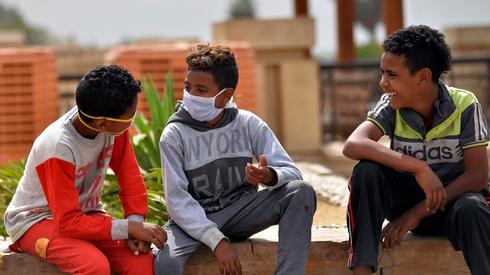 Niños egipcios usan máscaras en la ciudad de Luxor