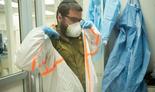 Un soldado de las FDI se pone un equipo de protección en un laboratorio militar que investiga el tratamiento del coronavirus.