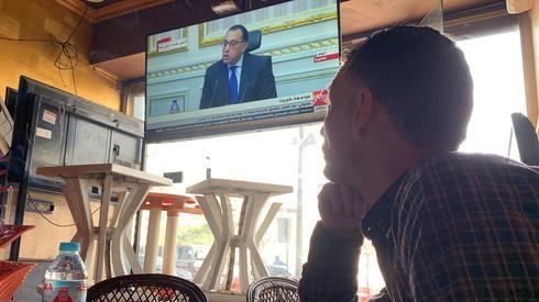 Hombre egipcio observa al primer ministro anunciando medidas para contrarrestar el coronavirus.