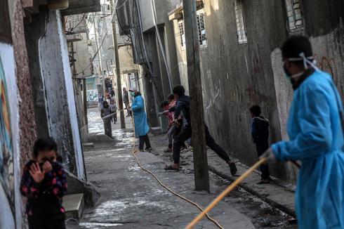 Trabajadores desinfectan un campo de refugiados en el centro de la Franja de Gaza.