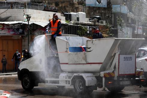 Empleados del municipio palestino rocían desinfectante en la ciudad de Hebrón.