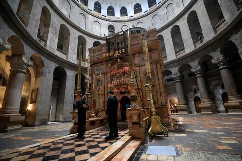Um padre ortodoxo grego e um zelador estão de pé em frente ao templo desolado da Igreja do Santo Sepulcro na cidade velha de Jerusalém.