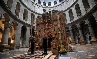 Un sacerdote ortodoxo griego y un cuidador se paran frente al edículo desierto en la Iglesia del Santo Sepulcro en la Ciudad Vieja de Jerusalem.