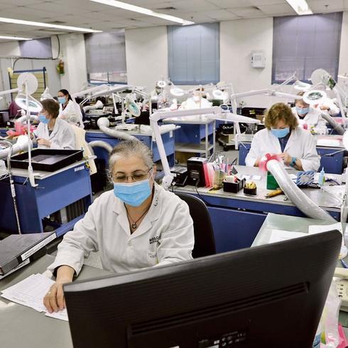 La líder del equipo analiza en la computadora el progreso de la producción.
