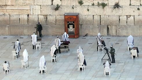 Un pequeño número de fieles judíos rezan durante la bendición sacerdotal para la Pascua en el Muro de los Lamentos, 12 de abril de 2020.