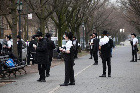Hombres judíos ultraortodoxos rezando mientras se mantienen alejados unos de otros en Brooklyn, Nueva York durante la pandemia de coronavirus,
