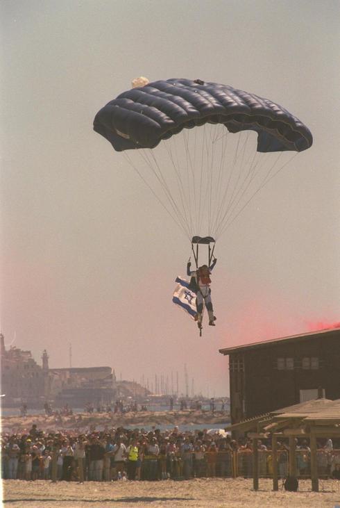 Tradición que aún continúa: un paracaídista baja con la bandera israelí en la playa de Tel Aviv, 2004.