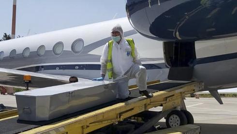 Un miembro del equipo voluntario de emergencia de ZAKA descarga un ataúd de un avión en el aeropuerto Ben Gurion en Israel