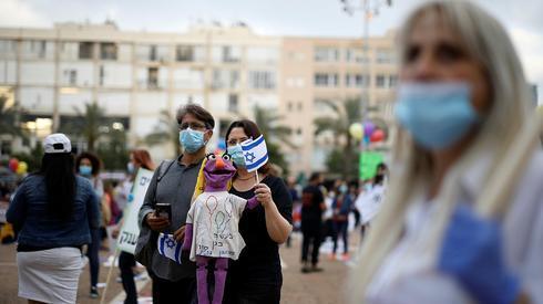 Gente que usa barbijos durante una protesta en Tel Aviv.
