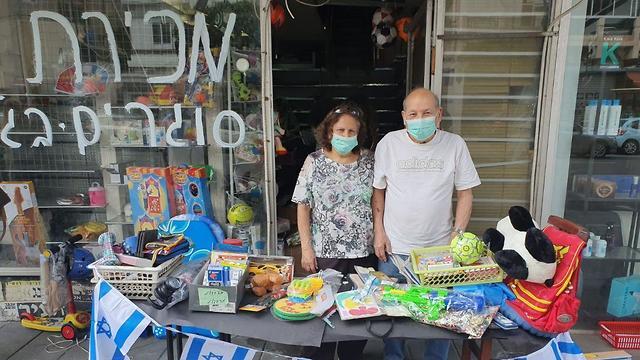 Una pareja en Tel Aviv cierra su comercio debido a la crisis del coronavirus.