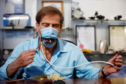 Una ranura en el barbijo permite el paso del tenedor con comida.