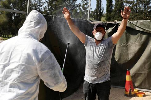 Trabajador sanitario palestino rocía desinfectante a un trabajador que regresa de Israel.