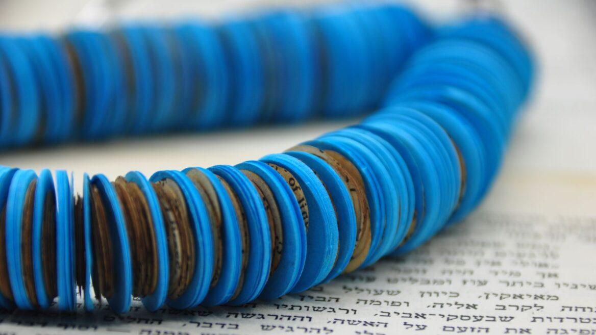 Una joya hecha de libros antiguos y papeles de colores por la artista israelí Hedva Klein.