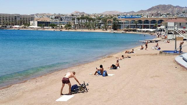 Turistas de Eilat, recostados en la arena y manteniendo la distancia.