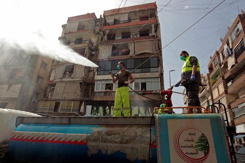 Trabalhadores libaneses pulverizam desinfetante contra o coronavírus.