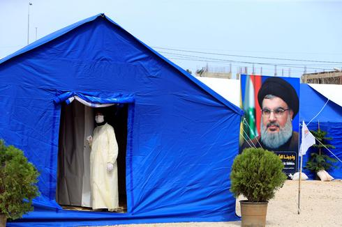 Hospital improvisado para lidar com o surto de coronavírus com uma imagem de Nasrallah ao lado.
