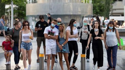 Los peatones, algunos con máscaras, se preparan para cruzar la calle en el Círculo Dizengoff de Tel Aviv.