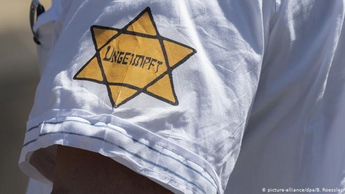 Un manifestante en Alemania con la estrella de David de tela amarilla, en la que aparece la expresión 'no inmune' en lugar de la palabra 'judío' que figuraba en la de la época nazi.