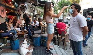 Una trabajadora verifica la temperatura de un cliente al ingresar a un bar en Tel Aviv.