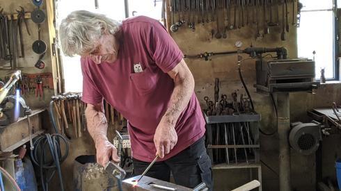 El artista Moshe Katz demuestra cómo realiza sus esculturas de metal.