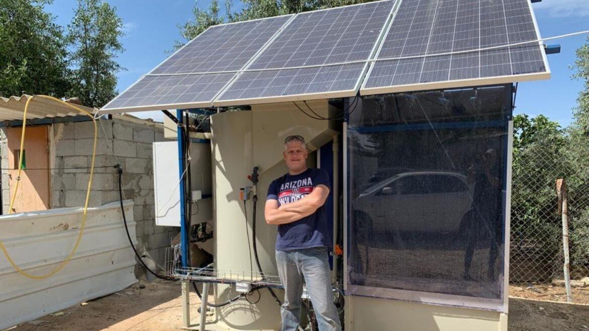 Clive Lipchin del Instituto Arava de Estudios Ambientales con el sistema de tratamiento de aguas residuales que se prueba en una aldea beduina.