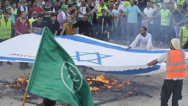 Partidarios de los Hermanos Musulmanes incendian prenden fuego una bandera de Israel en Jordania durante la operación 'Margen Protector' de las FDI en Gaza.