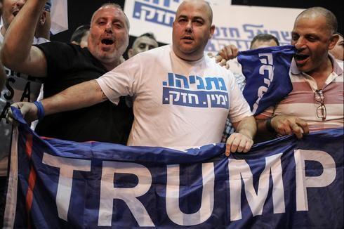 Simpatizantes del Likud sostienen una bandera de apoyo a Trump.