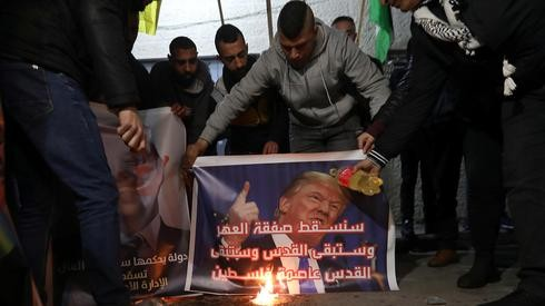 Manifestantes palestinos queman imagen de Trump en una protesta contra el plan de paz de Estados Unidos.