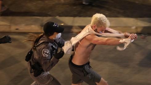 Un manifestante es perseguido por una policía en Jerusalem.