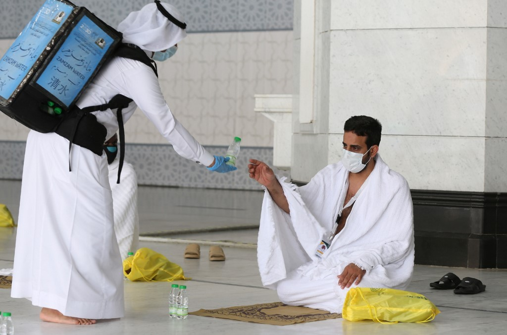 Un peregrino musulmán recibe agua en la Gran Mezquita de La Meca.