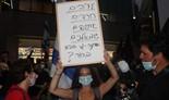 """Eliana Barbel en la protesta en Tel Aviv con un cartel que dice: """"árabes, haredim, etíopes, zurdos. Ohana, ¿quién es el próximo en la fila?"""