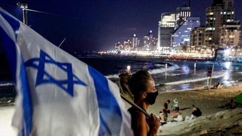 Una manifestante lleva una bandera de Israel en una protesta en Tel Aviv.