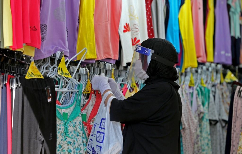 Una mujer iraní con máscara de protección y guantes en una tienda de Teherán.