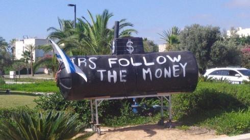Un cartel colocado frente a la casa particular de Netanyahu alude a la presunta corrupción en los gastos de defensa.